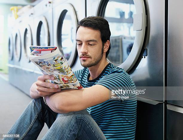 man reading a comic book in a laundromat - comic book stock pictures, royalty-free photos & images
