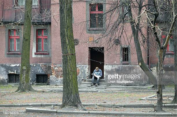 Man reading a newspaper in front of a house in the miners housing estate of Bytom