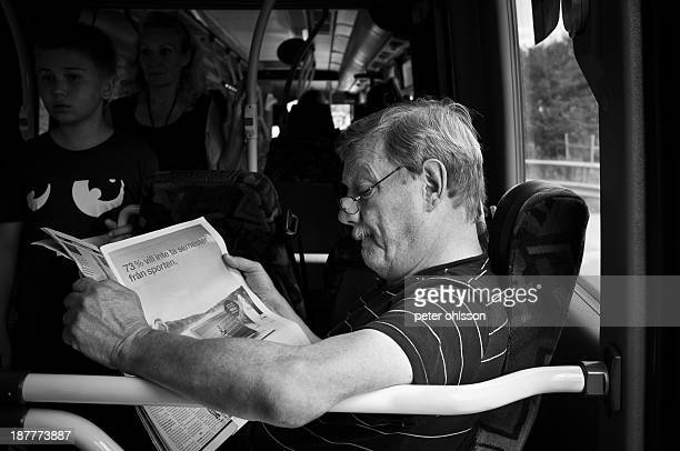 CONTENT] Man reading a newspaper on the bus