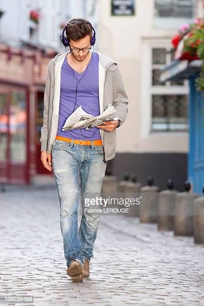 Man reading a newspaper on the street, Paris, Ile-de-France, France