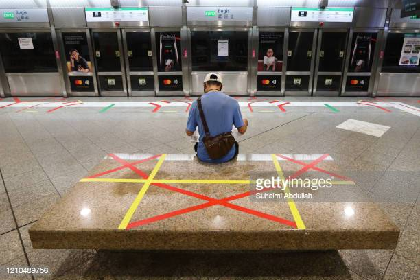 Man reading a newspaper sits on an unmarked safety distancing marker at a train station on April 21, 2020 in Singapore. Singapore recorded a daily...