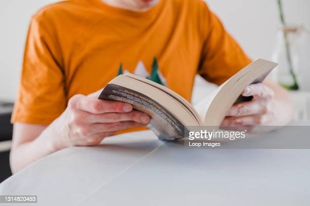 Man reading a novel at home.