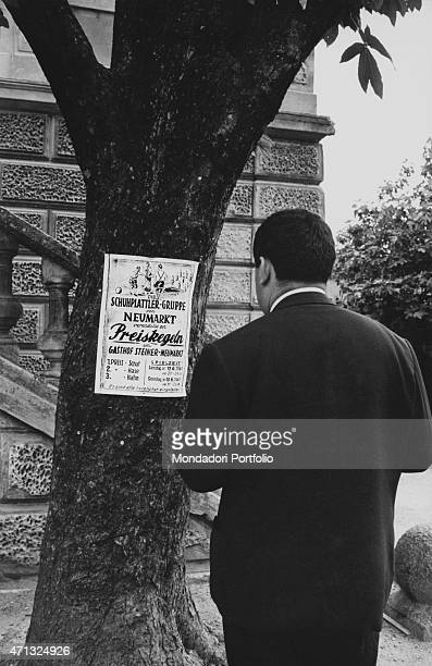Man reading a poster in German showing the fares of the Gasthof Steiner bowling. German irredentists stroke terror into the village to force Italian...