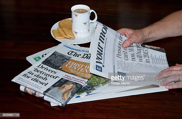 Man reading a Saturday newspaper on dining room table with a mug of coffee and plate of biscuits
