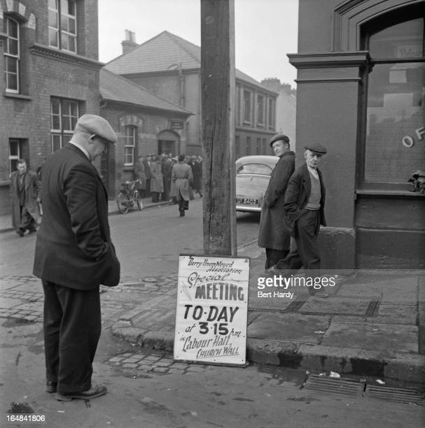 A man reading a sign advertising a special meeting of the Derry Unemployed Association in Derry Northern Ireland 25th November 1955 Original...