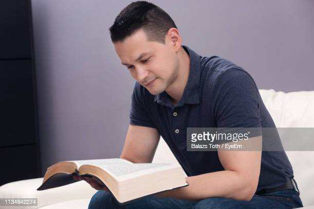 man reading bible at home - religious text stock pictures, royalty-free photos & images