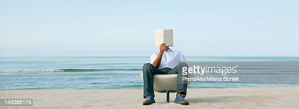 Man reading book at the beach