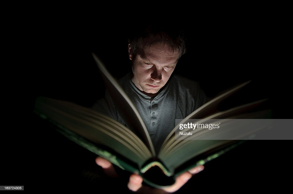 Man Reading Book Illuminated by Light : Stock Photo