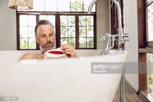 man reading book in bathtub - taking a bath stock pictures, royalty-free photos & images