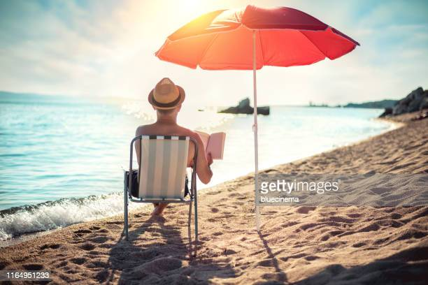 man reading book in deck chair under sun umbrella near sea - parasol stock pictures, royalty-free photos & images