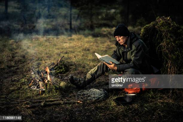 man reading book in forest - survival stock pictures, royalty-free photos & images