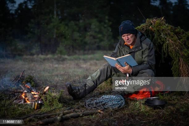 森の中で本を読む男 - 生存 ストックフォトと画像