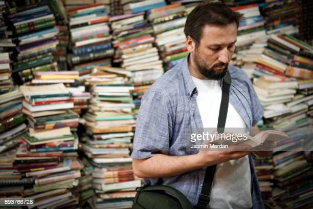 Man reading book in library of old books