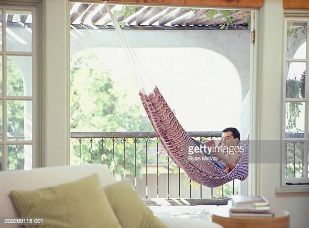 Man reading book, lying in hammock on balcony