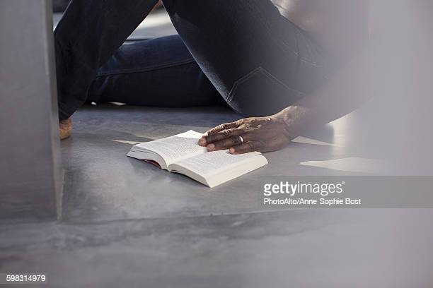 Man reading book on floor, cropped
