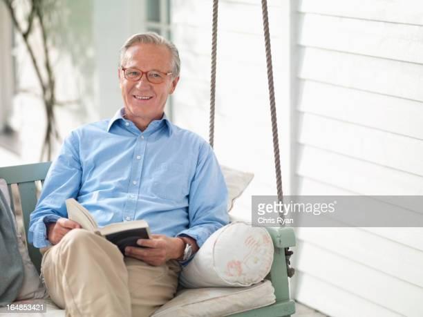 Mann liest ein Buch auf Verandaschaukel