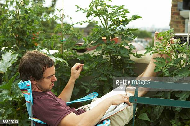 Man reading book on roof terrace