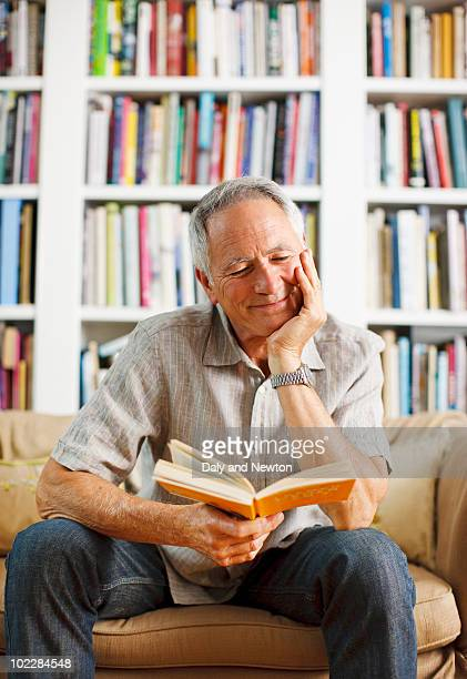 Man reading book on sofa