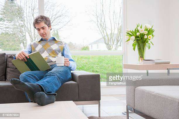 man reading book on sofa with feet up - men in white socks stock photos and pictures
