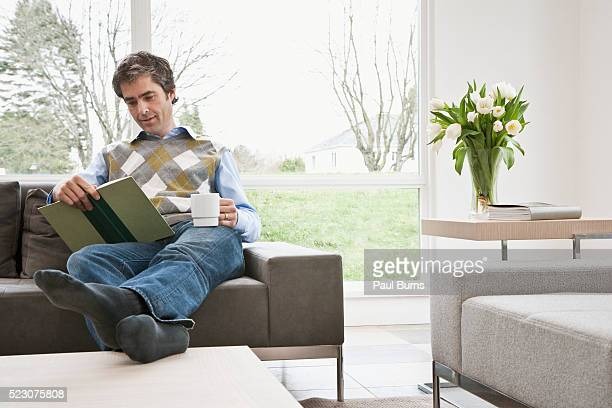 Man reading book on sofa with feet up
