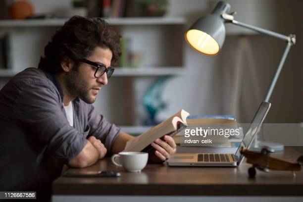 man reading book on the table - book stock pictures, royalty-free photos & images