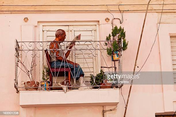 Man reading book on tiny balcony