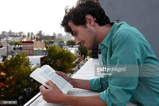 Man reading book outdoors, profile