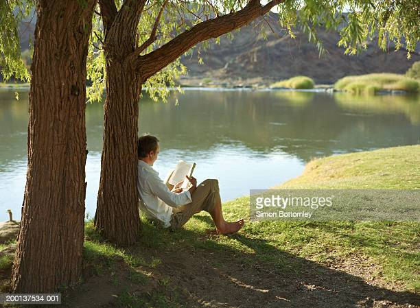 Man reading book under tree by river