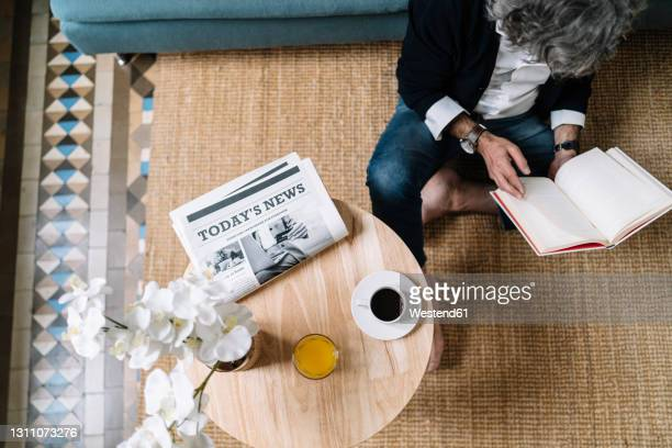 man reading book while coffee and juice by newspaper on wooden table at home - paper stock pictures, royalty-free photos & images