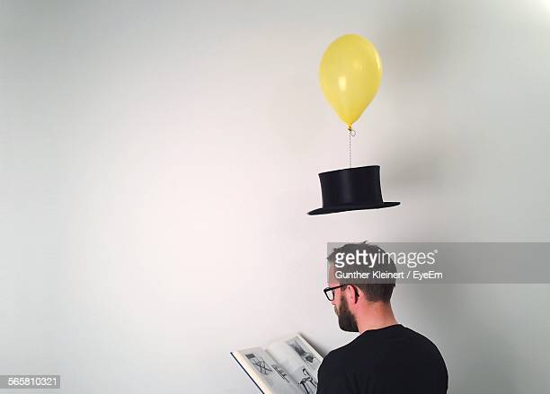 Man Reading Book While Hat Tied To Balloon Over White Background