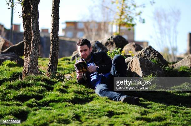 Man Reading Book While Lying Down On Field