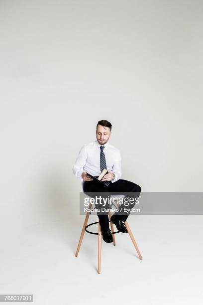 Man Reading Book While Sitting On Chair Against White Background