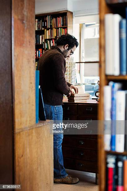 Man reading book while standing seen from shelves