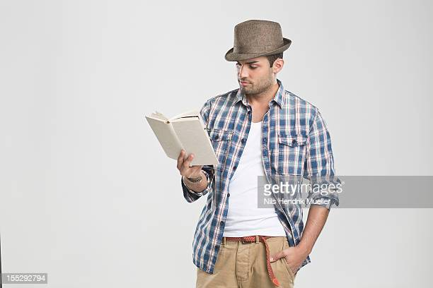 Man reading book with hand in pocket