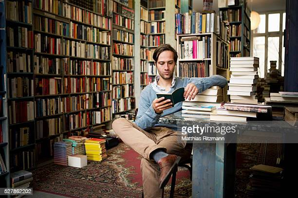 Man reading books in bookstore