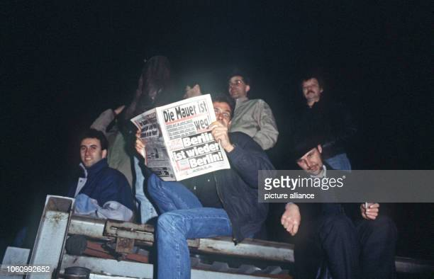 A man reading 'BZ' tabloid sits on the Berlin Wall as the border is opened in East Berlin GDR 10 November 1989
