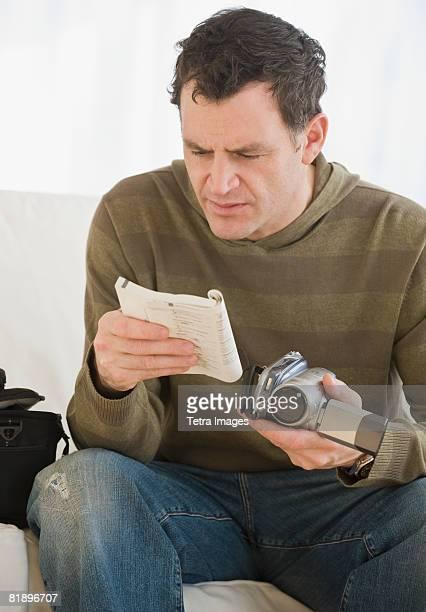 Man reading camera manual