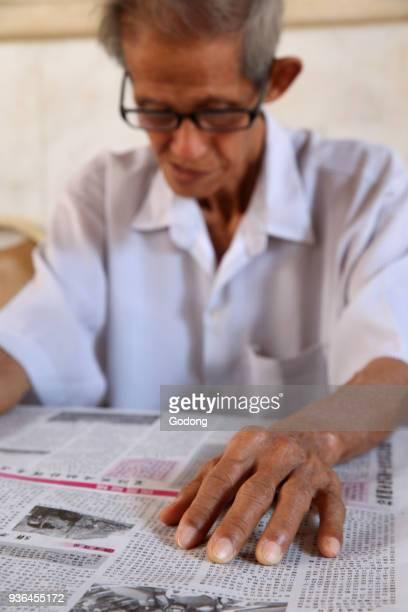 Man reading chinese newspaper Ho Chi Minh City Vietnam