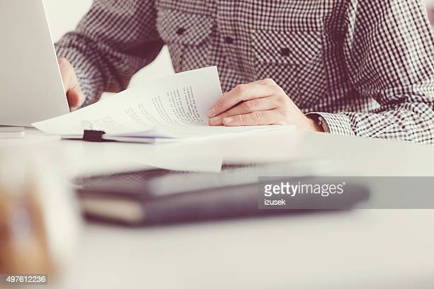 Man reading documents and using laptop, unrecognizable person