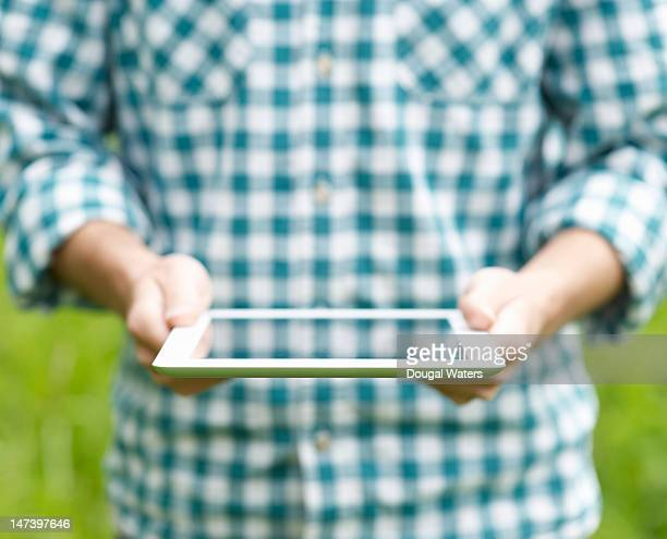 man reading from a digital tablet in a field - newtechnology stock pictures, royalty-free photos & images