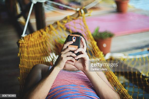 man reading from a smart phone in a hammock - ilha de mabul imagens e fotografias de stock