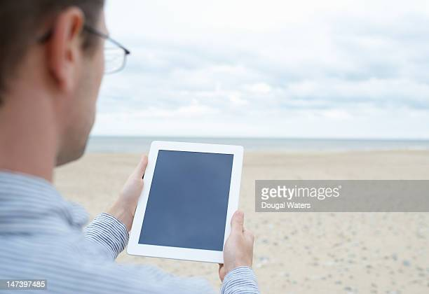 Man reading from tablet in front of sea scape.