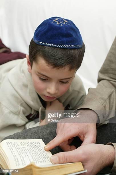 man reading hebrew to boy - keppeltje stockfoto's en -beelden