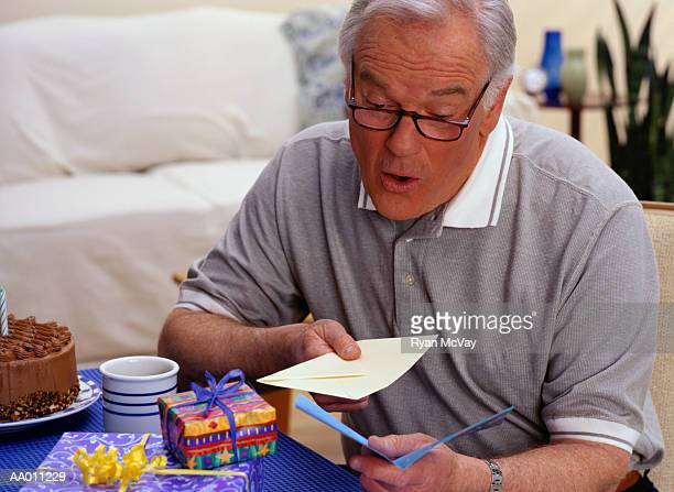 man reading his birthday cards - birthday card stock pictures, royalty-free photos & images