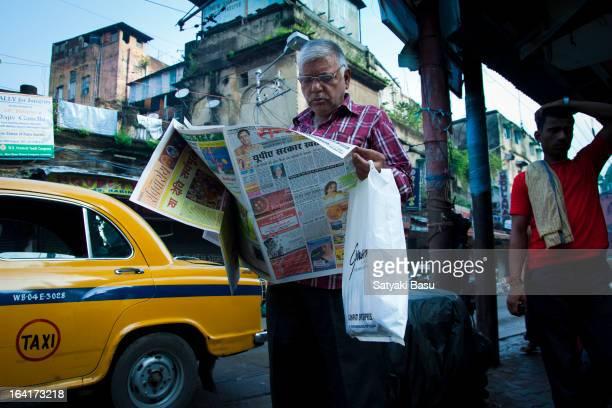 Man reading his morning newspaper in the streets of north Kolkata, India.