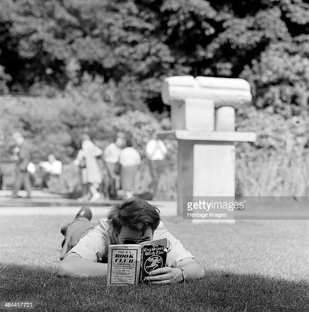 Man reading in a park London 19621964 A man lying engrossed in a book with a modern sculpture in the background in an unidentified London park