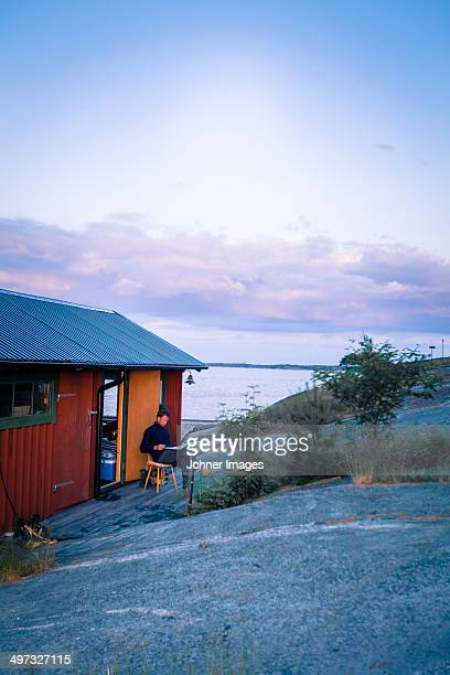 man reading in front of weekend cottage, moja, sweden - archipelago stock pictures, royalty-free photos & images