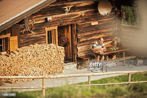 Man reading in porch of log cabin