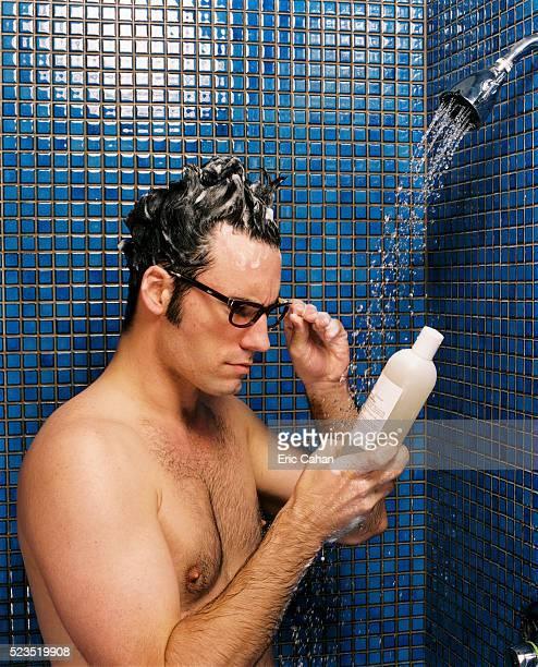Man Reading Instructions on Shampoo Bottle