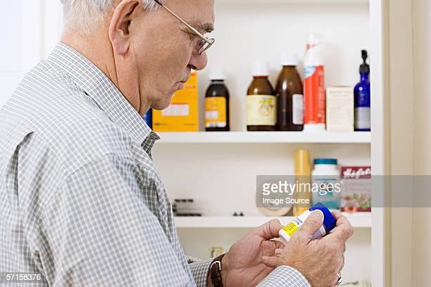 Mann Lesung Tablet-label auf Flasche